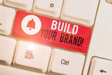 Text sign showing Build Your Brand. Business photo showcasing creates or improves customers knowledge and opinions of product White pc keyboard with empty note paper above white background key copy space