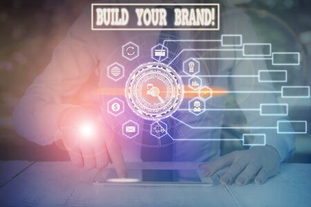Writing note showing Build Your Brand. Business concept for creates or improves customers knowledge and opinions of product Woman wear formal work suit present using smart latest device 版權商用圖片