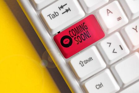 Word writing text Coming Soon. Business photo showcasing event or action that will happen after really short time White pc keyboard with empty note paper above white background key copy space