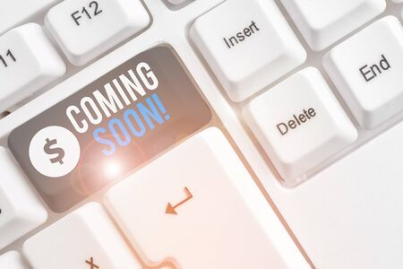 Text sign showing Coming Soon. Business photo showcasing event or action that will happen after really short time White pc keyboard with empty note paper above white background key copy space Stok Fotoğraf
