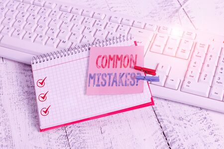 Writing note showing Common Mistakes Question. Business concept for repeat act or judgement misguided making something wrong notebook reminder clothespin with pinned sheet light wooden