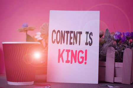 Word writing text Content Is King. Business photo showcasing marketing focused growing visibility non paid search results Flowers and stationary plus plain sheet with paper big cup above a table
