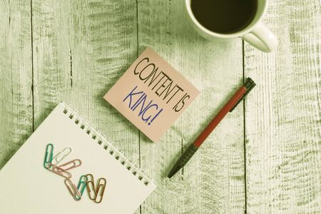 Text sign showing Content Is King. Business photo showcasing marketing focused growing visibility non paid search results Stationary placed next to a cup of black coffee above the wooden table Stockfoto