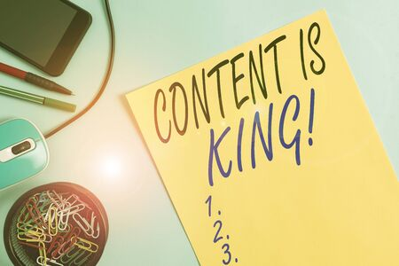 Writing note showing Content Is King. Business concept for marketing focused growing visibility non paid search results Notebook and stationary with gadgets above pastel backdrop