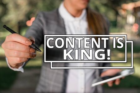 Conceptual hand writing showing Content Is King. Concept meaning marketing focused growing visibility non paid search results Outdoor background with business woman holding lap top and pen