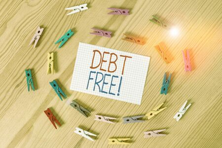 Text sign showing Debt Free. Business photo text does not owning any money or things to any individual or companies Colored clothespin papers empty reminder wooden floor background office Stok Fotoğraf