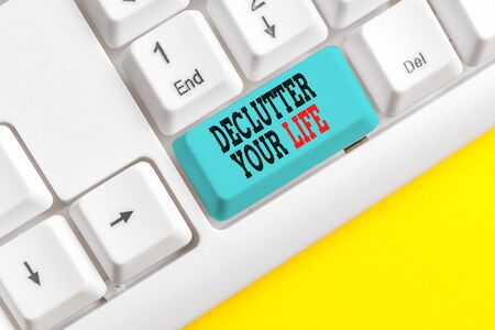 Text sign showing Declutter Your Life. Business photo text To eliminate extraneous things or information in life White pc keyboard with empty note paper above white background key copy space Stok Fotoğraf