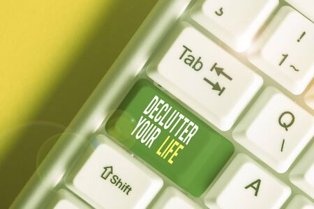 Text sign showing Declutter Your Life. Business photo showcasing To eliminate extraneous things or information in life White pc keyboard with empty note paper above white background key copy space