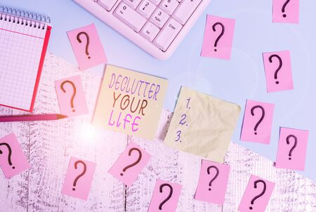 Text sign showing Declutter Your Life. Business photo text To eliminate extraneous things or information in life Writing tools, computer stuff and math book sheet on top of wooden table