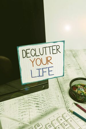 Word writing text Declutter Your Life. Business photo showcasing To eliminate extraneous things or information in life Note paper taped to black computer screen near keyboard and stationary