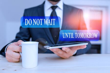 Writing note showing Do Not Wait Until Tomorrow. Business concept for needed to do it right away Urgent Better do now Male human wear formal clothes present use hitech smartphone