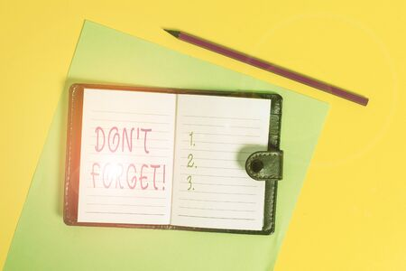Text sign showing Don T Forget. Business photo showcasing used to remind someone about important fact or detail Dark leather private locked diary striped sheets marker colored background