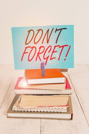 Handwriting text writing Don T Forget. Conceptual photo used to remind someone about an important fact or detail pile stacked books notebook pin clothespin colored reminder white wooden