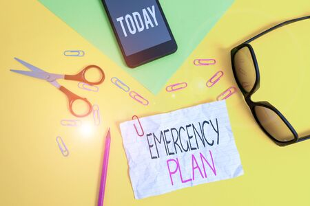Conceptual hand writing showing Emergency Plan. Concept meaning procedures for handling sudden or unexpected situations Paper sheets smartphone scissors eyeglasses colored background Stock fotó