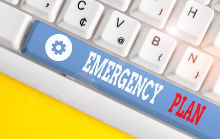Conceptual hand writing showing Emergency Plan. Concept meaning procedures for handling sudden or unexpected situations White pc keyboard with note paper above the white background