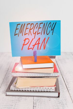 Handwriting text writing Emergency Plan. Conceptual photo procedures for handling sudden or unexpected situations pile stacked books notebook pin clothespin colored reminder white wooden Stock fotó