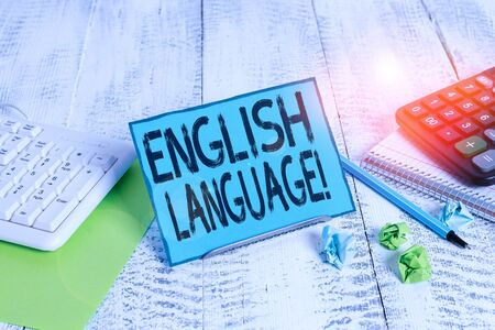 Text sign showing English Language. Business photo showcasing third spoken native lang in world after Chinese and Spanish Notepaper stand on buffer wire in between computer keyboard and math sheets