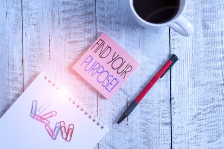Text sign showing Find Your Purpose. Business photo showcasing reason for something is done or for which still exists Stationary placed next to a cup of black coffee above the wooden table