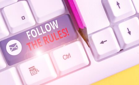 Writing note showing Follow The Rules. Business concept for go with regulations governing conduct or procedure White pc keyboard with note paper above the white background