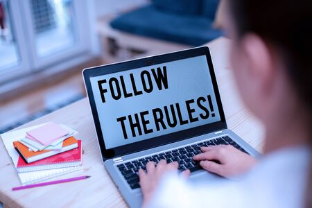 Text sign showing Follow The Rules. Business photo showcasing go with regulations governing conduct or procedure woman laptop computer office supplies technological devices inside home