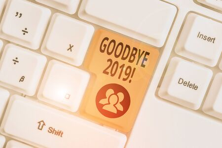 Conceptual hand writing showing Goodbye 2019. Concept meaning express good wishes when parting or at the end of last year White pc keyboard with note paper above the white background Stock Photo