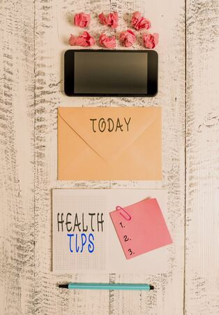 Handwriting text writing Health Tips. Conceptual photo advice or information given to be helpful in being healthy Envelop smartphone notepad note clip marker paper balls wooden background