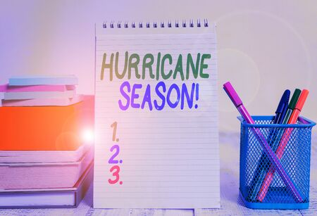 Text sign showing Hurricane Season. Business photo text time when most tropical cyclones are expected to develop Pens metal holder stacked note pads books square box spiral wooden table