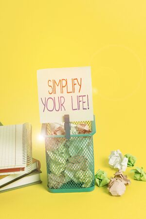 Handwriting text writing Simplify Your Life. Conceptual photo focused on important and let someone else worry about less ones Trash bin crumpled paper clothespin empty reminder office supplies yellow