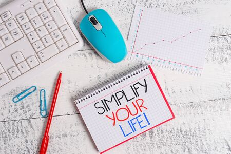 Writing note showing Simplify Your Life. Business concept for focused on important and let someone else worry about less ones Wood desk office appliance computer equipaments charts paper slot
