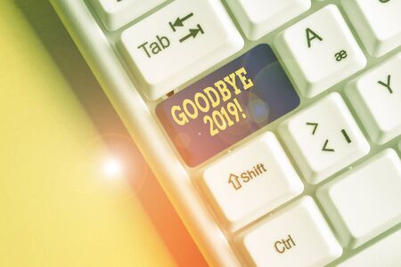 Word writing text Good Bye 2019. Business photo showcasing express good wishes when parting or at the end of last year White pc keyboard with empty note paper above white background key copy space