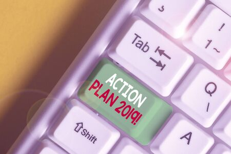 Writing note showing Action Plan 2019. Business concept for proposed strategy or course of actions for current year White pc keyboard with note paper above the white background