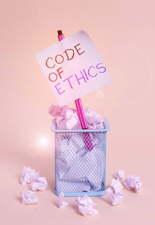 Writing note showing Code Of Ethics. Business concept for basic guide for professional conduct and imposes duties crumpled paper and stationary with paper placed in the trash can