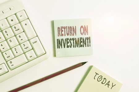Text sign showing Return On Investment. Business photo showcasing perforanalysisce measure used evaluate efficiency of investment White pc keyboard with empty note paper and pencil above white background