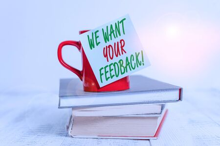 Conceptual hand writing showing We Want Your Feedback. Concept meaning criticism given someone say can be done for improvement Coffee cup sticky note stacked books retro old retro wooden table