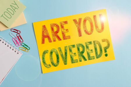 Conceptual hand writing showing Are You Covered Question. Concept meaning asking showing if they had insurance in work or life Cardboard and writing equipment placed above pastel backdrop