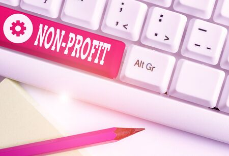 Word writing text Non Profit. Business photo showcasing not making or conducted primarily to make profit organization White pc keyboard with empty note paper above white background key copy space
