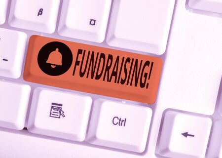 Text sign showing Fundraising. Business photo text seeking to generate financial support for charity or cause White pc keyboard with empty note paper above white background key copy space