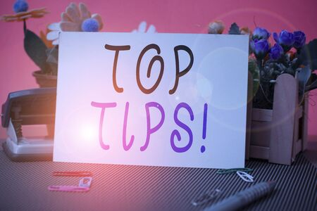 Conceptual hand writing showing Top Tips. Concept meaning small but particularly useful piece of practical advice Flowers and writing equipments sheet above textured backdrop