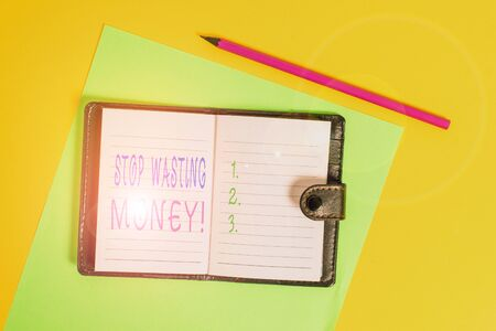 Text sign showing Stop Wasting Money. Business photo showcasing advicing demonstrating or group to start saving and use it wisely Dark leather private locked diary striped sheets marker colored background