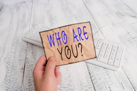 Conceptual hand writing showing Who Are You Question. Concept meaning asking about someone identity or demonstratingal information Man holding colorful reminder square shaped paper wood floor