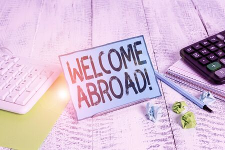 Text sign showing Welcome Abroad. Business photo showcasing something that you say when someone gets on ship Notepaper stand on buffer wire in between computer keyboard and math sheets