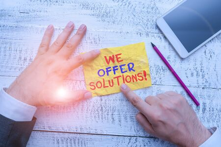 Word writing text We Offer Solutions. Business photo showcasing way to solve problem or deal with difficult situation Hand hold note paper near writing equipment and modern smartphone device