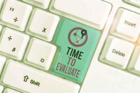 Konzeptionelle Handschrift zeigt Zeit zu bewerten. Begriff Sinne etwas in Bezug auf seinen Wert oder seine Bedeutung beurteilen Weiße PC-Tastatur mit Notizpapier über dem weißen Hintergrund Standard-Bild