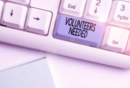 Writing note showing Volunteers Needed. Business concept for need work or help for organization without being paid White pc keyboard with note paper above the white background