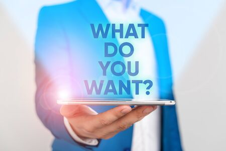 Writing note showing What Do You Want Question. Business concept for say or write in order to ask demonstrating about something Man in the blue suite and white shirt holds mobile phone in the hand