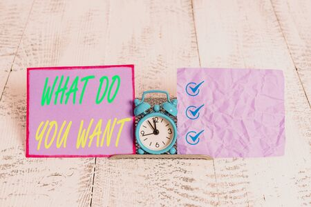 Text sign showing What Do You Want. Business photo text used for offering something to someone or asking their need Mini blue alarm clock standing above buffer wire between two notation paper