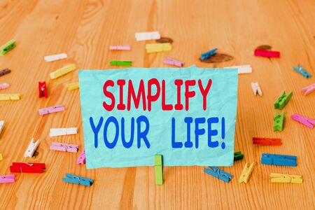 Word writing text Simplify Your Life. Business photo showcasing focused on important and let someone else worry about less ones Colored clothespin papers empty reminder wooden floor background office Foto de archivo - 132519413