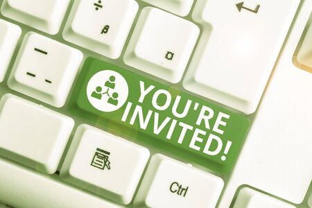 Writing note showing You Re Invited. Business concept for make a polite friendly request to someone go somewhere White pc keyboard with note paper above the white background