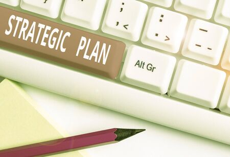 Text sign showing Strategic Plan. Business photo text a systematic process of envisioning a desired future White pc keyboard with empty note paper above white background key copy space