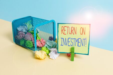 Conceptual hand writing showing Return On Investment. Concept meaning perforanalysisce measure used evaluate efficiency of investment Trash bin crumpled paper clothespin reminder office supplies